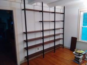 The shelves don't touch the wall. Each wooden shelf is firmly attached to the brackets with four screws.